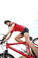 Germany, Bavaria, Young woman riding mountain bike