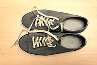 A pair of grey sneakers on a wooden floor