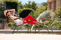Woman resting in a chair near a pond, Bassin octogonal, Jardin des Tuileries, Paris, Ile_de_France, France