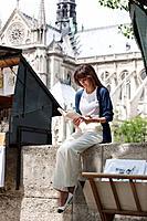 Woman reading a book at a book stall, Notre Dame de Paris, Paris, Ile_de_France, France