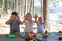 Caucasian children making peanut butter bird feeders