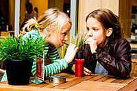 2 girls drinking some juice