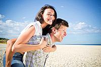 Caucasian man giving girlfriend piggyback ride on beach