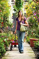 Caucasian woman pulling wagon in plant nursery