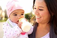 Mixed race mother watching baby girl drinking bottle