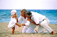 Grandparents with their granddaughter on the beach