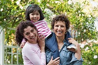 Smiling Hispanic grandmother, mother and daughter
