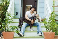 Mixed race man sitting on front stoop with dogs