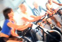 People on exercise bikes at health club