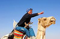 Tourist caressing his camel on a ride, Sahara desert, Libya