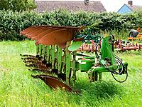 An old plough in a grass field