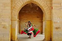 Lady dancing at Gadsisar Gadisar lake structure , Jaisalmer , Rajasthan , India MR772C