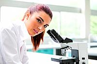 Brunette posing with a microscope while looking at the camera