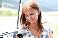headshot of young woman resding test message on mobile phone