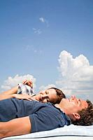 young couple lying on roof of car