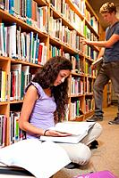 Portrait of a student reading a book while her classmate is choosing a book in a library