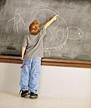 Little Boy Drawing on Chalkboard