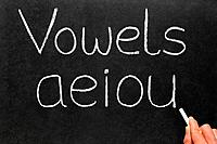 A teacher writing the five vowels letters on a blackboard.