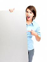 Portrait of a surprised young female pointing at empty billboard