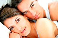 Closeup portrait of a sweet young couple relaxing on the bed