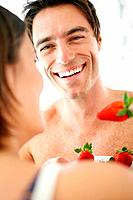 Portrait of a happy young couple eating strawberries together