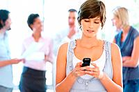 Young woman sending text message with people in background