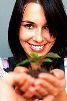 Focus on woman smiling while presenting plant