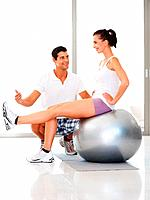 Happy young woman exercising on fitness ball with personal trainer