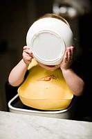 Boy wearing bib eating from bowl