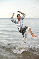 Excited Man with Cell Phone in Surf