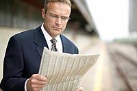 Businessman Reading Newspaper on Railroad Platform