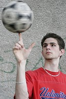 young man balancing a ball on a finger, Germany