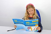 schoolgirl reading happily in a English book