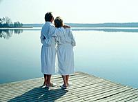 Mature couple wearing bathrobes embracing by a lake