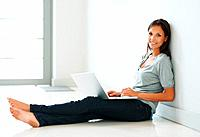 Pretty woman sitting against wall with laptop