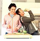 Two Young Men Preparing Artichokes in Kitchen