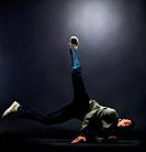 Portrait of a young male bboy balancing on hand against grunge background