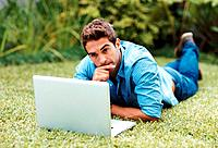 Portrait of a handsome young man thinking while using laptop in a park _ Outdoor