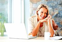 Portrait of a cheerful middle aged woman with laptop and a tea cup