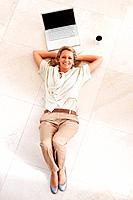 Top view of a smiling middle aged woman lying on floor by laptop and tea cup