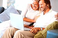 Cheerful mature man and woman looking at laptop screen on couch at home