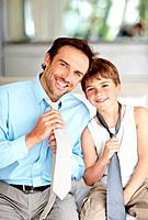 Portrait of a happy young father and son showing their necktie and smiling _ Indoor