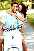Portrait of young romantic couple having fun on a scooter in a park _ Outdoor