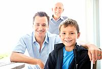 Closeup portrait of a cute small boy smiling with his father and grandfather