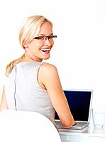 Portrait of attractive young business woman using laptop and smiling at office