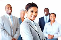 Portrait of successful female leader smiling with business team in background