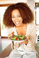 Young woman with curls eating salad