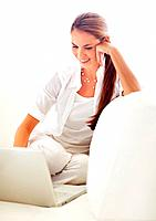 Portrait of smiling young woman working on laptop while sitting at home
