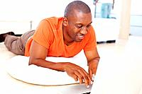 Happy African American man using laptop while lying on floor