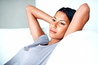 Closeup of beautiful mixed race woman resting on couch in deep thought